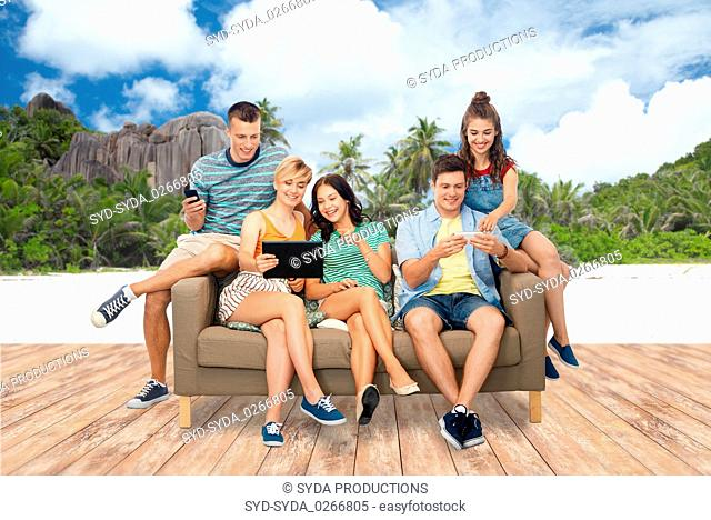 friends with tablet pc and smartphones over beach
