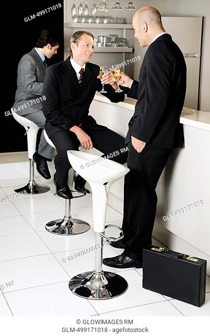 Two businessmen toasting with wine in a bar