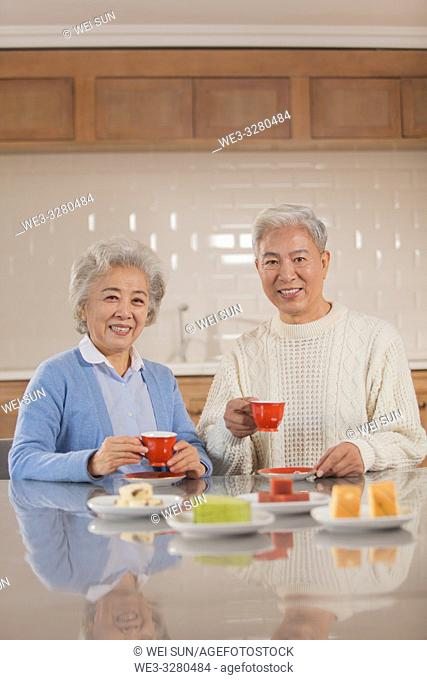 Happy old couple drinking tea in the kitchen, Chinese ethnicity