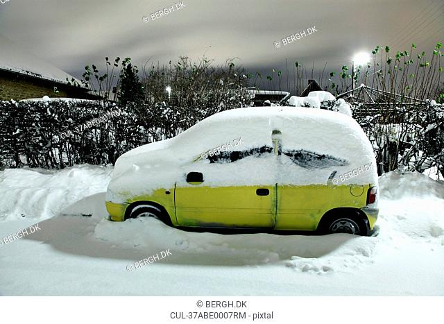 Snow covered car in driveway