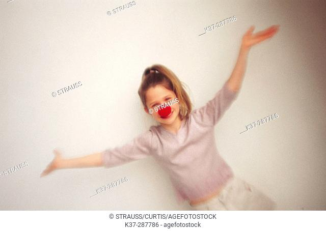 Young girl with clown nose portrait