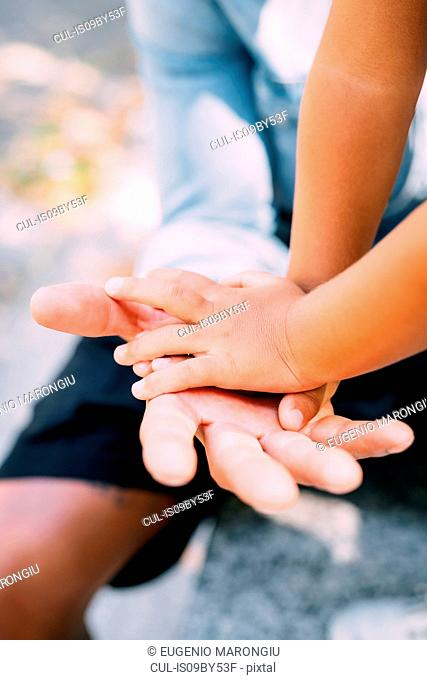 Toddler placing both hands on father's palm