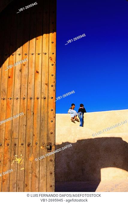 Two children at the Porte de la mer gate in the bastion walls of the Portuguese town in el Jadida, Atlantic Morocco