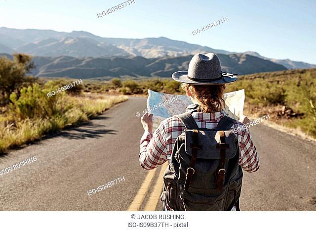 Woman standing in desert road, looking at map, Sedona, Arizona, USA