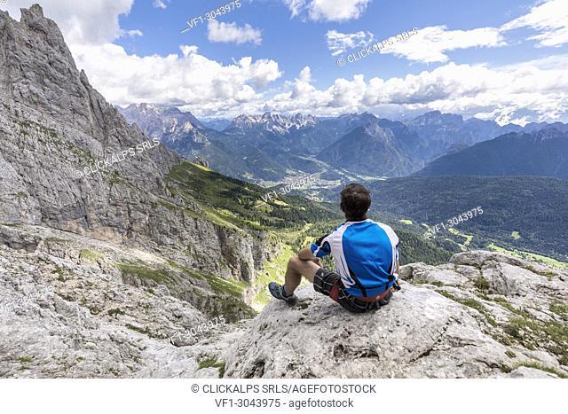 Europe, Italy, Veneto, Agordino, Mountaineer observes the panorama at the end of the ferrata Stella Alpina on Mount Agner, Pale di San Martino, Dolomites