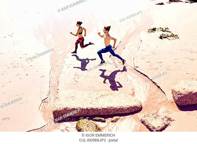 Young man and woman running along beach, elevated view