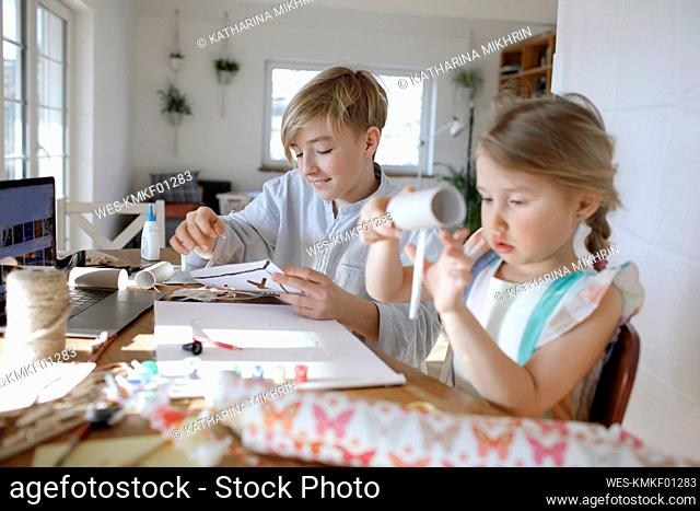 Boy and his little sister tinkering at home