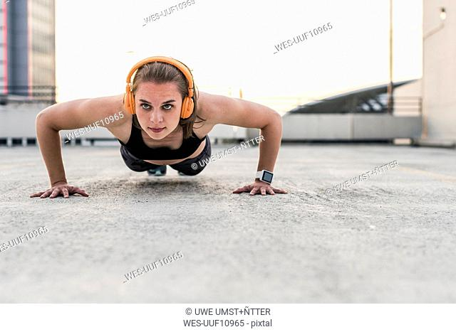 Woman with headphones doing pushups on parking level in the city