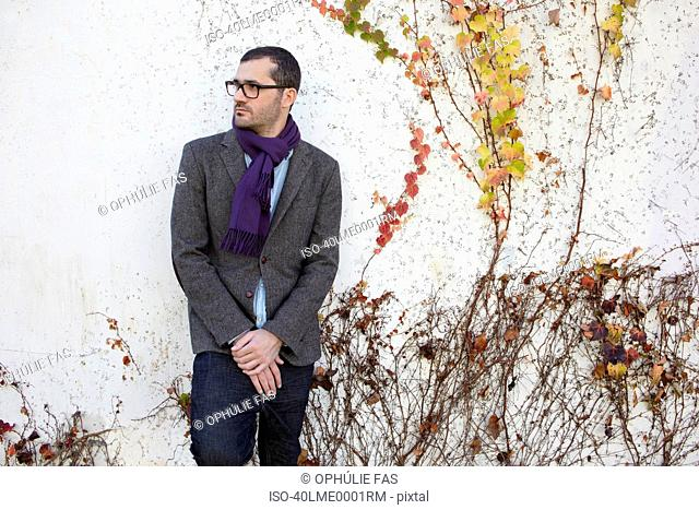 Man leaning against vine-covered wall