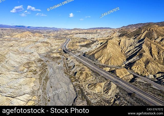 Bare ridges of eroded sandstone in the Tabernas Desert, Europe's only true desert. Transected by the A92 highway. Aerial view. Drone shot