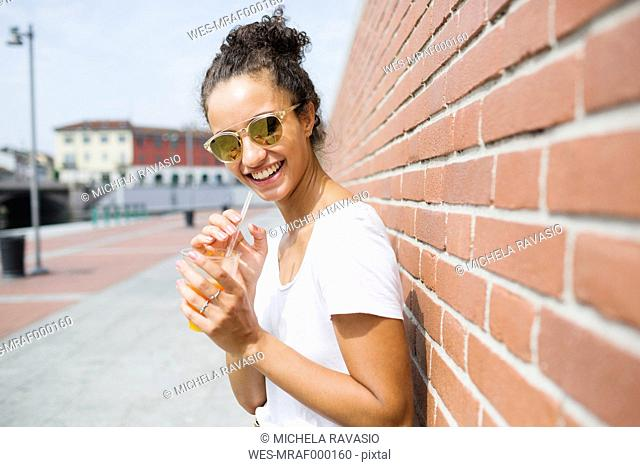 Happy young woman leaning against a brick wall holding orange juice
