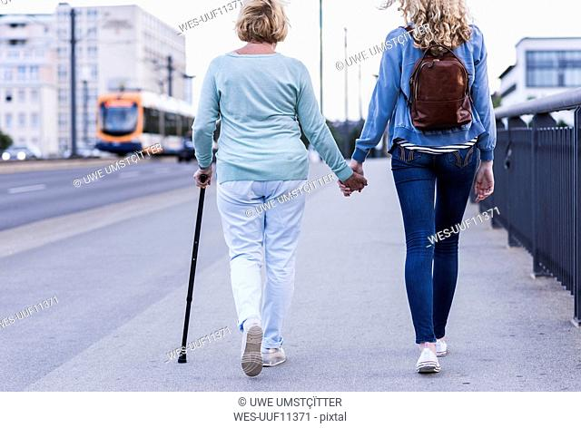 Back view of grandmother and granddaughter walking side by side