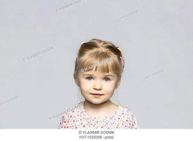 Portrait of cute girl against gray background