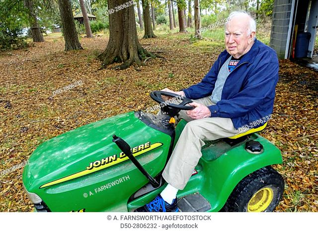 Retired man on lawn mower. Prince Frederick, Maryland, USA