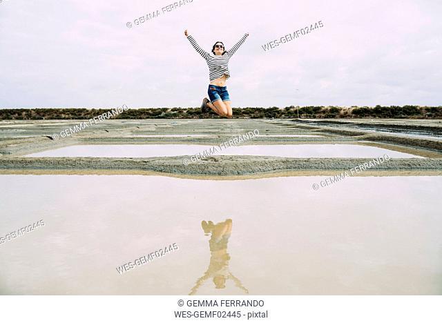 France, Bretagne, Marais salants de Guerande, Woman jumping