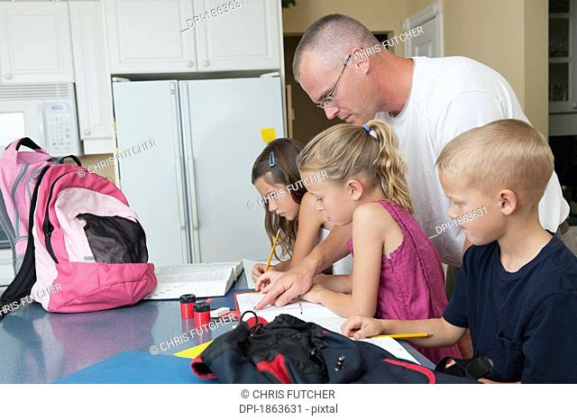 A father helping his children with their homework
