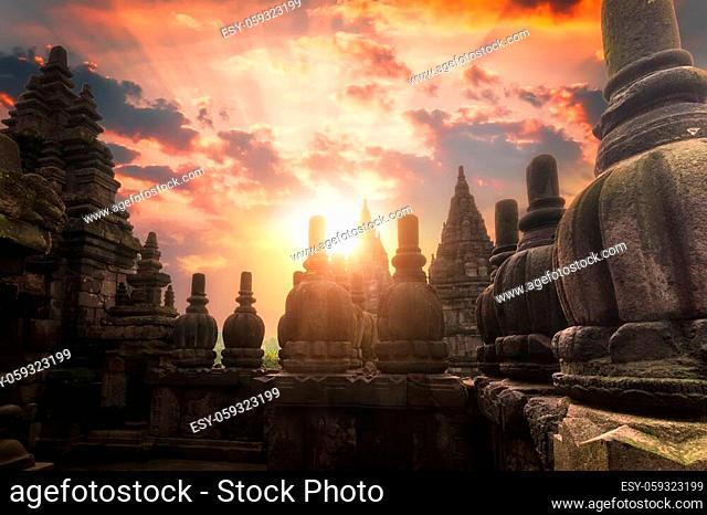 Rising sun shining behind Candi Prambanan or Rara Jonggrang Hindu temple located near Yogyakarta, Java, Indonesia. Beautiful shot with morning sunrise and...