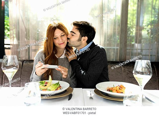 Man kissing woman taking a cell phone picture in a restaurant