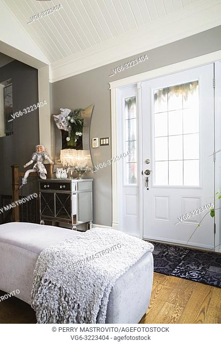 Ottomans, metal and glass topped mirror cabinet and Christmas decorations in entryway inside an old renovated circa 1840 Canadiana cottage style home