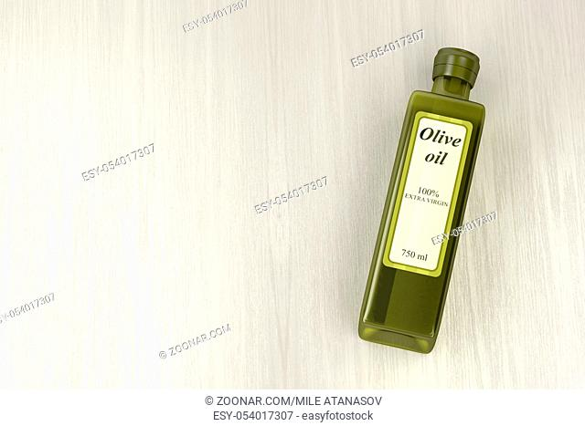 Extra virgin olive oil bottle on wooden table, top view
