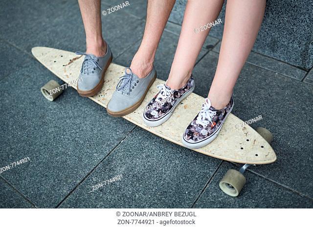 Feet couple of teenagers on the longboard closeup