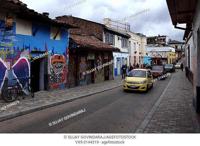 Bogotá, Colombia - May 28, 2017: Traffic drives past some Street Art and Graffiti in the historic La Candelaria district in the capital city of Bogota