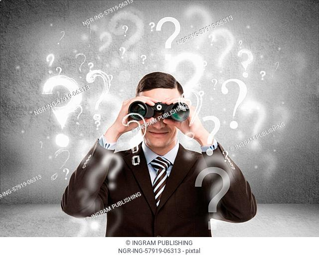 Handsome business man with binoculars and question marks above his head