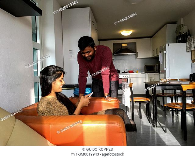 Aachen, Germany. Young, Indian Student's couple talking in their dormatory kitchen, while diner is cooking