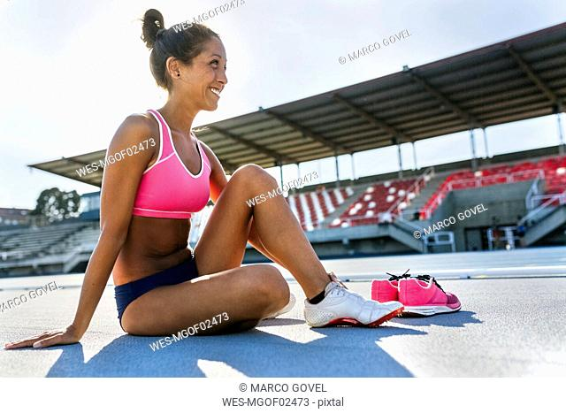 Athlete in stadium changing shoes
