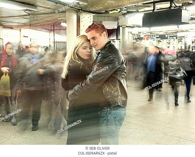 Romantic young couple hugging in New York City subway station, New York, USA