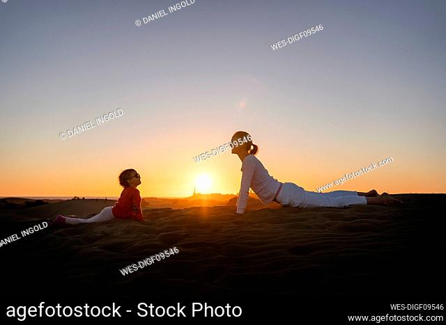 Mother and daughter practicing yoga in sand dunes at sunset, Gran Canaria, Spain