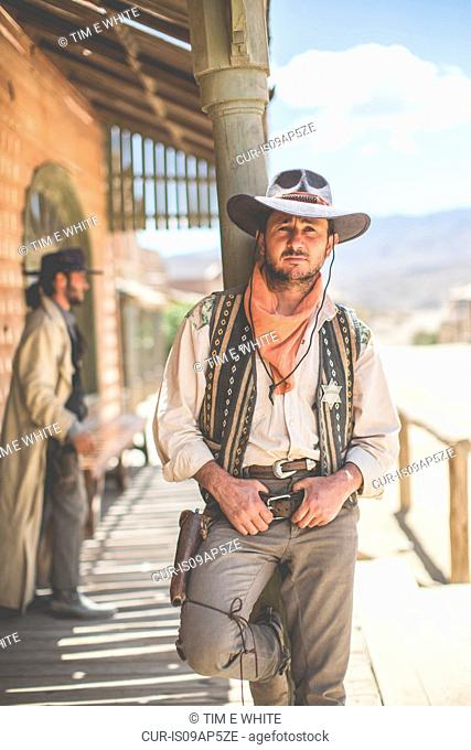 Portrait of cowboy leaning against pillar on wild west film set, Fort Bravo, Tabernas, Almeria, Spain