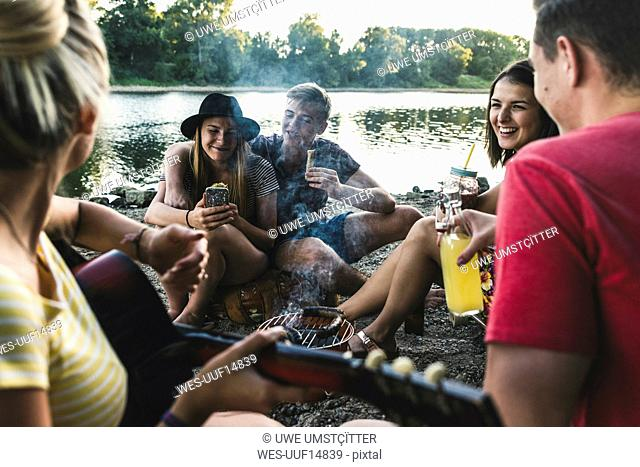 Group of friends sitting together having a barbecue at the riverside