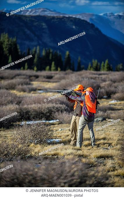 Female hunter showing male partner how to aim hunting rifle, Colorado, USA