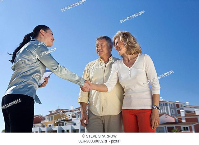 Real estate agent greeting mature couple