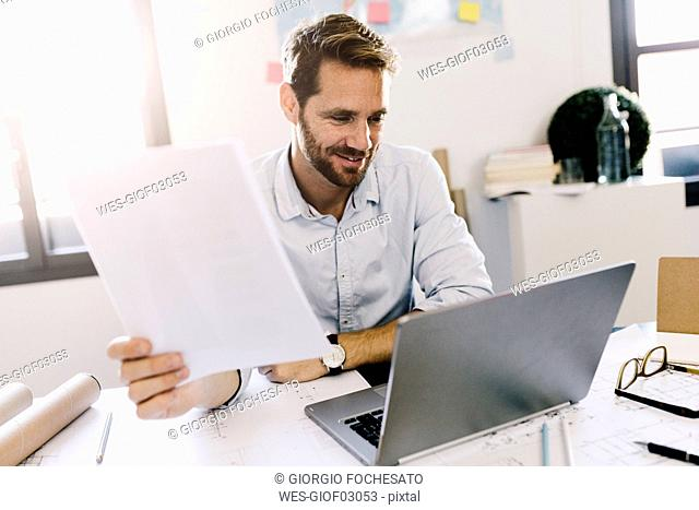 Smiling architect looking at laptop in his office
