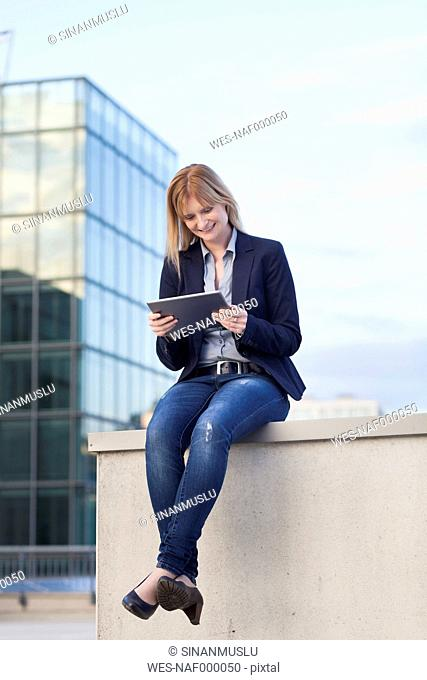 Smiling businesswoman sitting on a wall looking at tablet