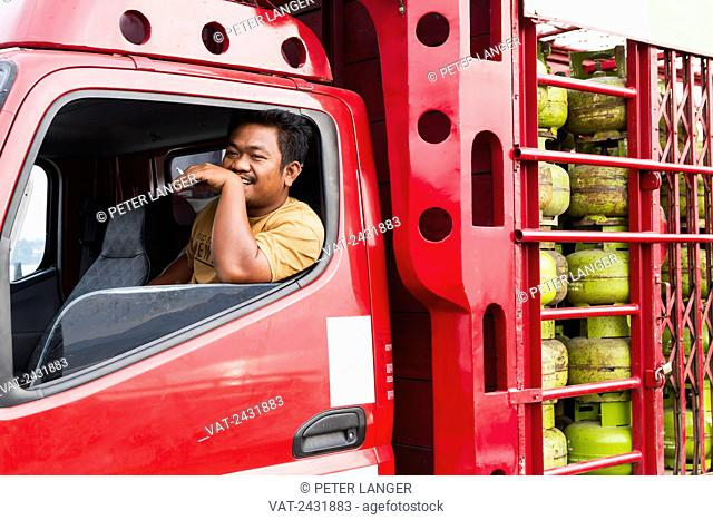 Truck driver smoking a cigarette in a truck with gas containers on board the car ferry between Parapat and Samosir Island, Lake Toba, North Sumatra, Indonesia