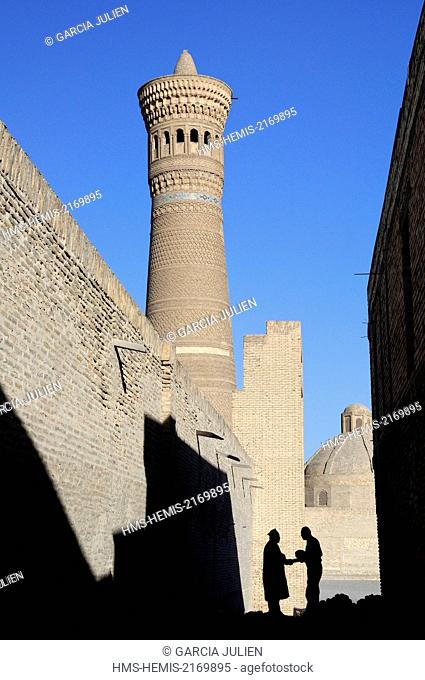 Uzbekistan, Bukhara, historic centre listed as World Heritage by UNESCO, silhouette of two men shaking hands in a small street near Kalon minaret