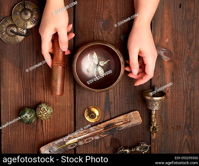 female hands hold a copper Tibetan singing bowl and a wooden stick, on the wooden table are items for alternative medicine, sound massage and meditation