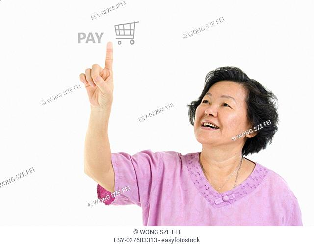 Portrait of Asian senior adult woman online shopping and finger pushing at check out pay button, isolated on white background