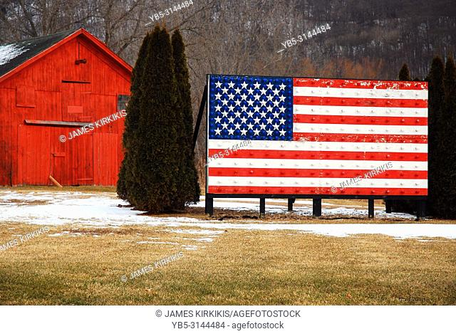A large American flag stands on a farm in rural New York