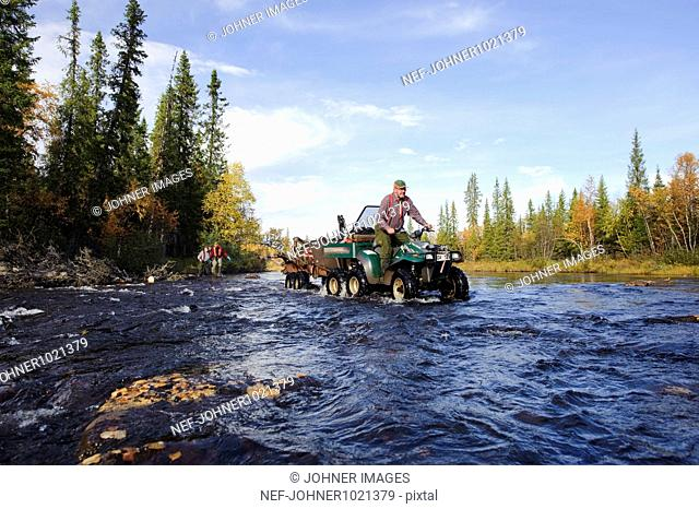 Man driving vehicle on creek in forest