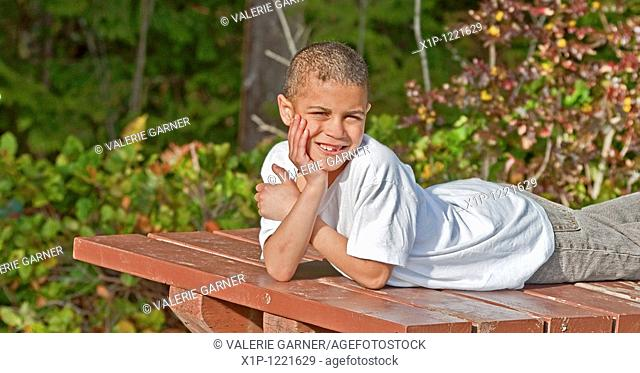 This 8 year old bi-racial boy is smiling outdoors in this portrait while lying on a picnic table with his hand on his face His missing teeth and bruised arm...
