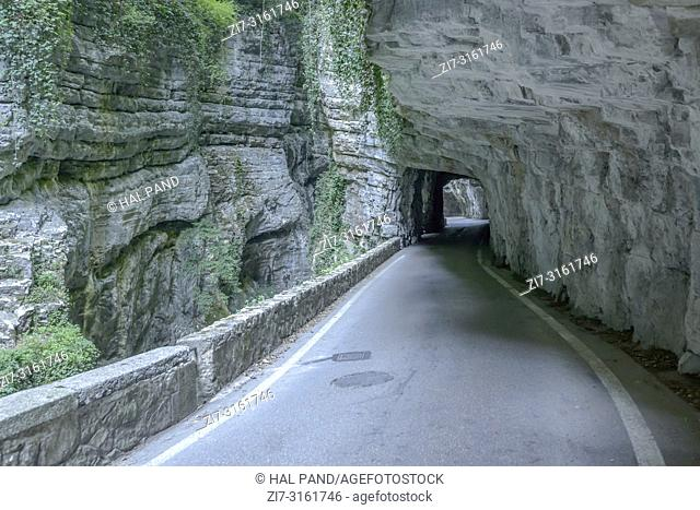rock walls flanking road and creek at bottom of Brasa gorge, shot in bright fall light at Tremosine, Brescia, Italy