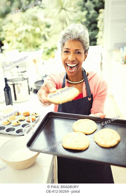 Portrait enthusiastic mature woman baking cookies in kitchen