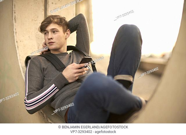 young model man relaxing in city, holding phone, in Hamburg, Germany