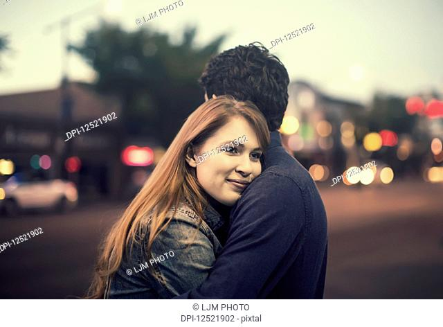 A young couple stands embracing on a sidewalk in a popular area at dusk; Edmonton, Alberta, Canada