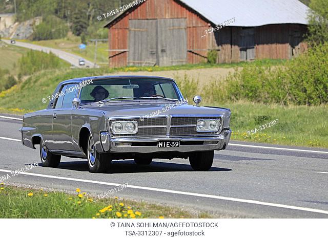 Salo, Finland. May 18, 2019. Classic grey Imperial car, mid 1960s, on road along rural highway to participate in the popular event Salon Maisema Cruising 2019