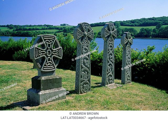 St Winnow church near Fowey. Celtic style headstones. Trees and sea in distance